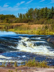 Foam water rapids on the smooth stones of the Winnipeg River. The concept of travel