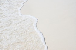 Foam wave and white sand on the beach. Sea wave on sand beach photo background. Coral beach sand with sea wave. White sand of oceanic coastline. Exotic island seaside banner with place for text.