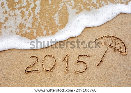Foaming sea wave coming to wash inscription of the year 2015 written in the wet yellow beach sand. Concept of celebrating the New Year at some exotic place #239106760