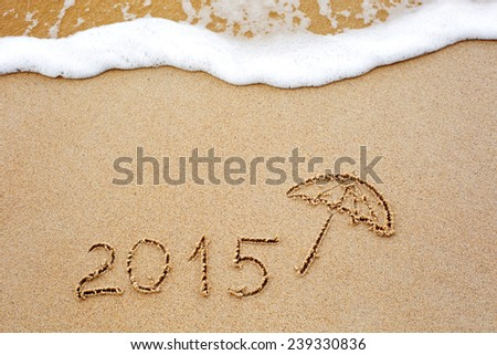 Foaming sea wave coming to wash inscription of the year 2015 written in the wet yellow beach sand. Concept of celebrating the New Year at some exotic place #239330836