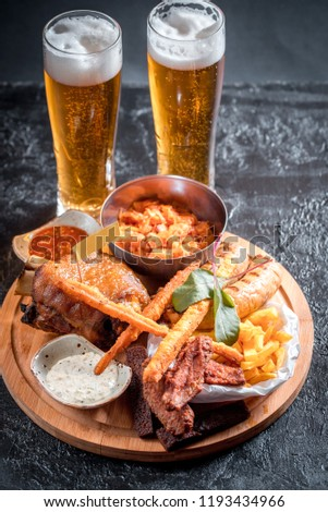 Foamy beer in a glass, hot appetizer, chicken wings, sauce in a beautiful served bowl. Catrofel and other deep-fried vegetables. unhealthy food. unhealthy food. many calories #1193434966