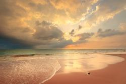 Foamy waves on sandy ocean beach under a beautiful sunset sky with clouds on Sri Lanka island.