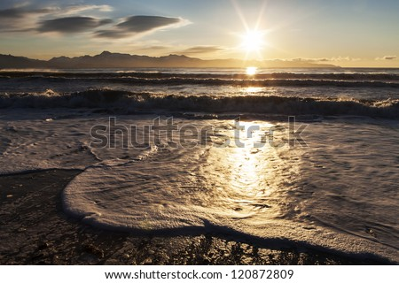Foamy waves washing up on an Alaskan beach with a sunburst and clouds.