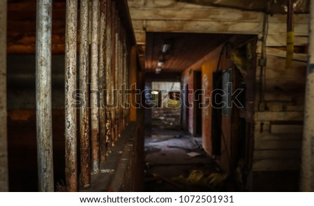Focal close up of rusting metal bars of an abandoned horse stall with faded distance of barn #1072501931