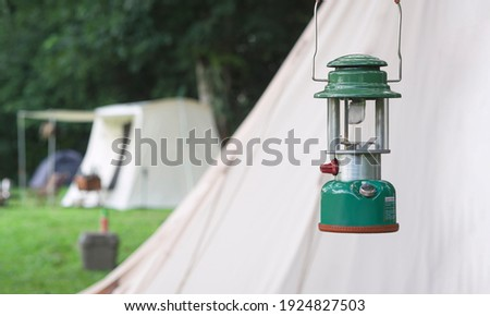 Focus at camping acetylene lantern with blurred background of field tents in camping area at natural parkland Stock photo ©