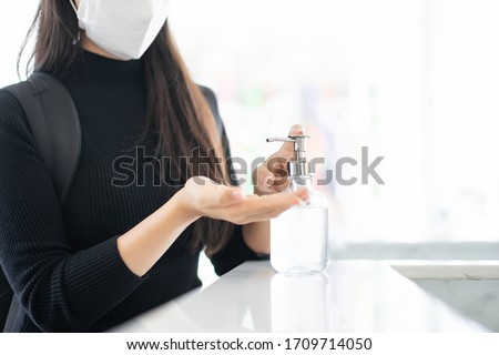 focus at woman hand washing alcohol gel in hotel front desk, protection policy for stop break out corona virus or covid 19 spread
