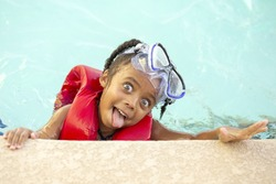 Focus is on the face of a young African American girl in a swimming pool with goggles on top of her head; she is making a silly face at the camera with her tongue sticking out.
