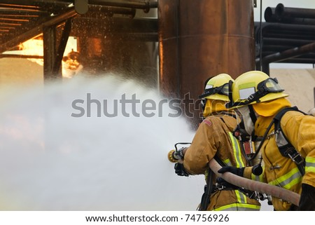 Focus is on the firefighter in the front holding the nozzle.