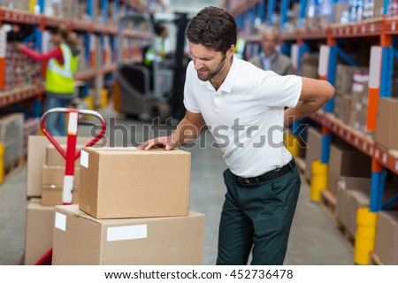 Focus of worker having a backache in a warehouse