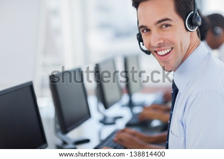 Focus on a joyful call centre agent with his headset