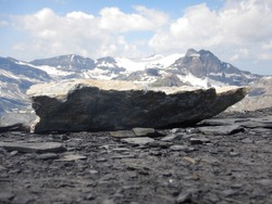Focus on a rough granite rock with glaciers and craggy Alpine peaks in the background in Swiss Alps