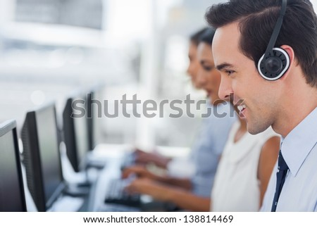 Focus on a smiling call centre agent working on computer