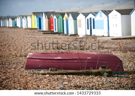 Focus on an upturned boat sitting on a shingle beach with a row of holiday beach huts blurred in the background.United Kingdom - Image