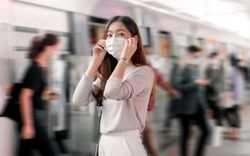 Focus on asian woman waring mask to protect virus while using public transportation and standing among many people. New Normal Concept.