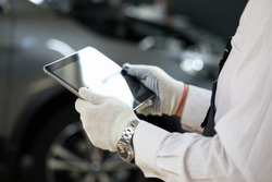Focus on automechanic hands in white gloves holding modern tablet near sportcar. Automotive checkup and service station concept. Empty copy space on screen