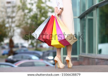 Focus on beautiful stylish female in stylish clothes and in high heel shoes holding multicolored packages. Fashion and shopping concept. Blurred background