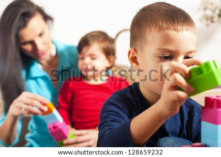 Focus on boy playing with cubes with mother and sister in background