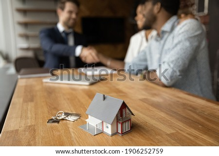 Focus on close up keys bunch and cottage house toy model on wooden table. Smiling young man broker realtor real estate agent shake hands of happy black couple clients homeowners on blurred background Photo stock ©