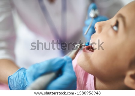 Focus on close-up of girl during dental treatment in medical office. She is opening her mouth while doctor is using instruments. Copy space in left side
