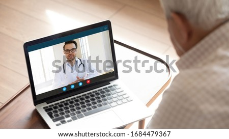Focus on computer screen with confident happy male family doctor general practitioner consulting giving advices to older mature worried man patient with sickness symptoms online via video call.