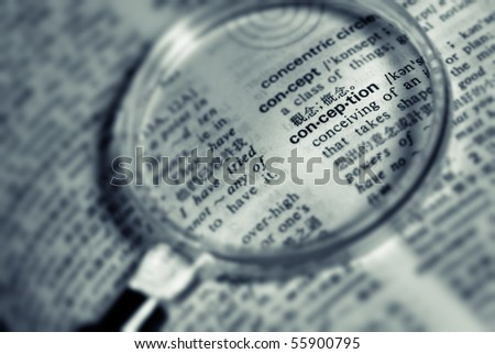 Focus on conception word with magnifier in book.