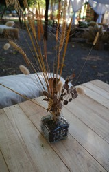 Focus on DIY glass vase of dried flower and dried plants on wooden table in the cafe