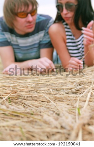 Focus on dry yellow autumn grass Happy couple in love is lying on hay background De focused pair faces with sunglasses Copy space for inscription