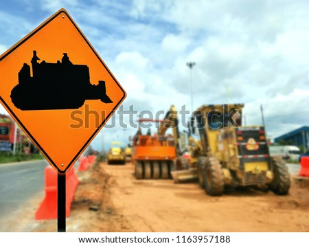 Focus on excavator road sign and blurred background of many excavators on the road improvement area in technology and development concept