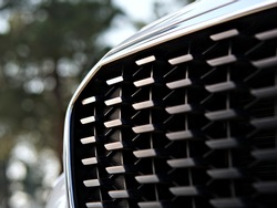 Focus on fashionable Radiator grill of a hybrid car, Close up, Blurred background