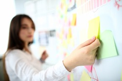 Focus on female hand attaching yellow stick with note to board. Lovely lady on full time job in office. Businesswoman and biz company concept. Copy space on stickers