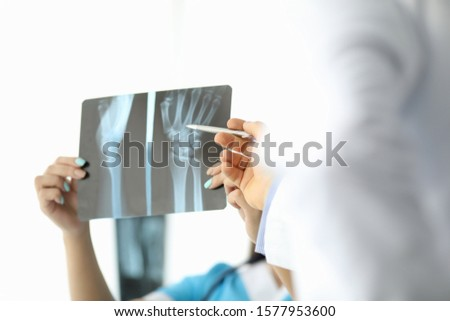 Focus on female hands holding skiagram of wrist. Professional surgeon pointing to bone fracture. Traumatologist discussing nature of patient injury. Medicine and healthcare concept Stock photo ©