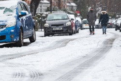 Focus on foreground of a snow covered street with blurred background of a walking couple in Crouch End area, North London