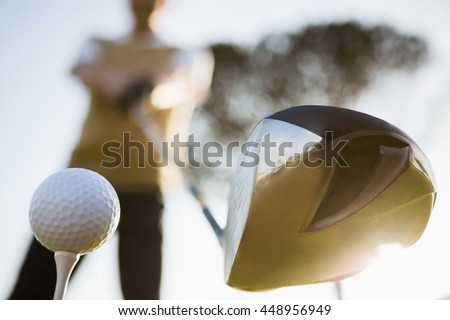 Focus on foreground of golf club and ball on a field