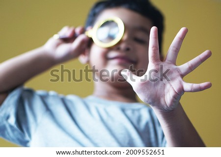 Focus on hands funny little Asian boy 4 year old looking through a magnifying glass.                                  Foto stock ©