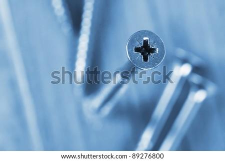 Focus on head of screw in lumber. Toned in blue