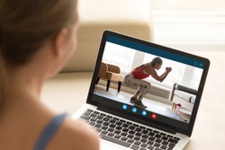 Focus on laptop screen with young woman in sportswear doing morning exercises, deep squats on yoga mat, staying fit at home. Interested girl watching online educational fitness workshop training.