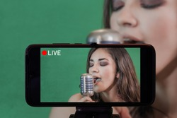 Focus on live view on smartphone on tripod, girl singing with microphone image on back screen with blurred scene in background. Social media live streaming concept