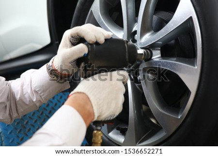 Focus on male automechanic hands using special automotive tool and carefully taking out titanic discs of expensive sport automobile. Automobile checkup concept #1536652271