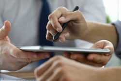 Focus on male hand pointing at screen of modern tablet with stylos. Biz colleagues discussing signing future bargain. Business negotiations concept. Blurred background