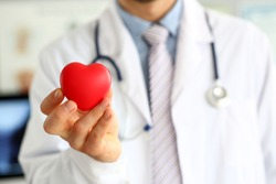 Focus on male hand with red heart-shaped symbol. Doctor wearing white uniform with stethoscope. Physician for prevent cardiovascular diseases. Medical treatment and healthcare concept