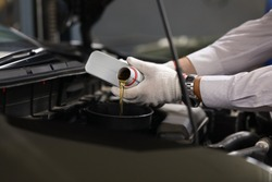 Focus on male specialist hands holding canister of machinery liquid and pouring under hood of sportcar with precise accuracy. Automotive checkup concept