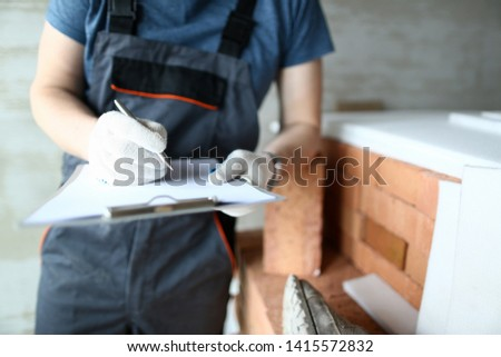 Focus on man with tablet writing outlay. Builder in protective outfit leaning on big pile of red bricks and checking everything workers need to start constructing. Building concept