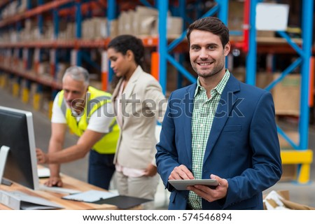 Focus on manager is smiling and holding a tablet in front of his colleagues in a warehouse #574546894