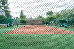 Focus on metal mesh fencing around the sports field, behind which you can see the tennis court and football goal on a cloudy summer day