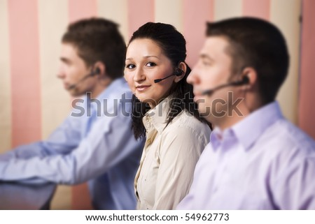 Focus on nice young woman customer service representative looking and smiling at you in the middle of two men team in office,vertical blinds background