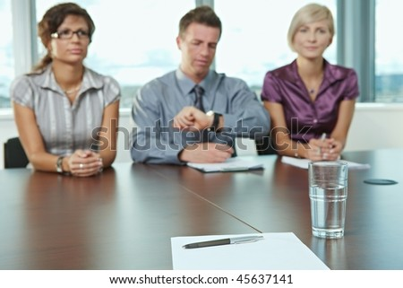 Focus on paper and pen on table. In the background panel of business people sitting conducting job interview.