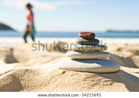 Focus on pile of pebbles with person exercising on the beach.