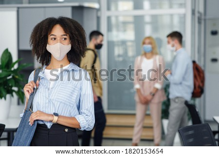 Focus on portrait of modern business african american woman came to work in morning. Colleagues in protective masks with bags in office interior are blurred background