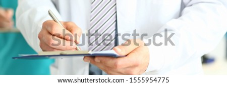 Focus on professional physician's hands writing something in notepad. Smart doc standing in clinic office. Man wearing lab coat and classy tie. Medical treatment and healthcare concept