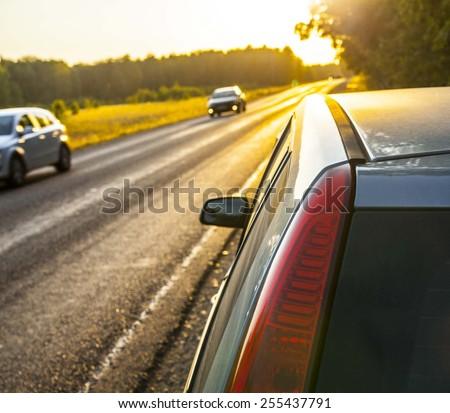 Focus on red headlight Stop car on the nature near asphalt highway road against evening sunset sky Sun rays shine through green trees summer forest Non urban scene